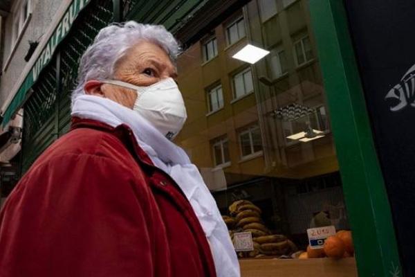 Una mujer espera en la entrada de un local comercial durante el estado de alarma provocado por la crisis del coronavirus